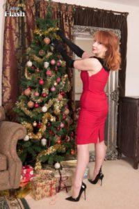 Red, knappe mature babe doet striptease bij de kerstboom
