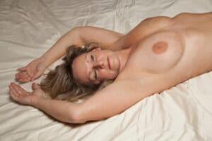 Rijpe vrouw met grote memmen ligt op bed